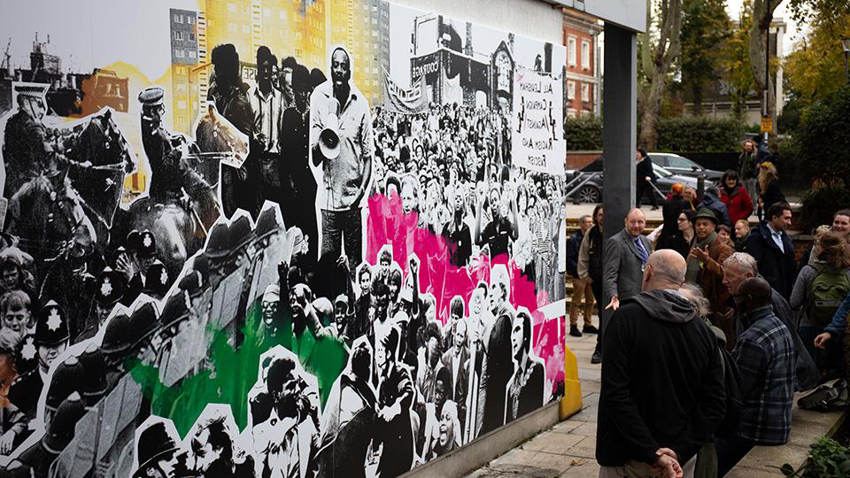 A photo of the mural and gathered crowd